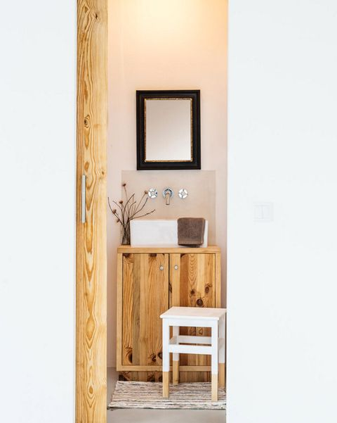 baño pequeño con mueble de lavabo y puerta de madera natural