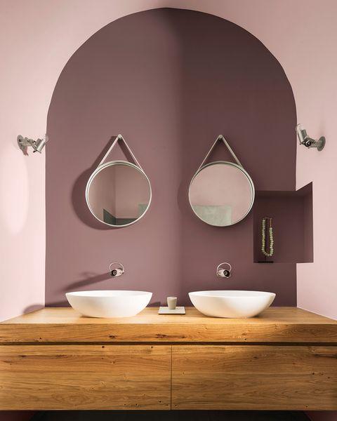 baño con dos lavabos y paredes en tonos rosa