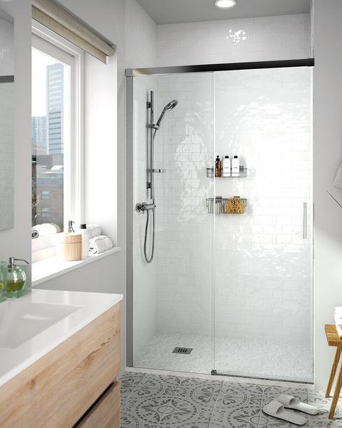 baño blanco con ducha de obra y suelo hidráulico