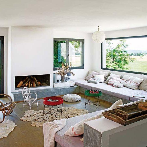 un salón con grandes ventanales y sofá de obra