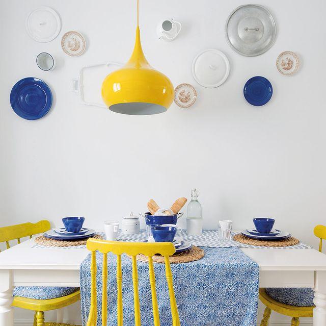 mesa de comedor blanca con sillas amarillas y mantel estampado azul