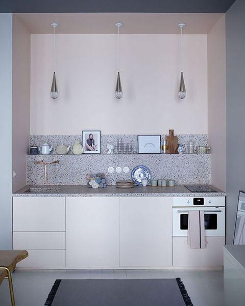 cocina pequeña con muebles blancos y pared de terrazo