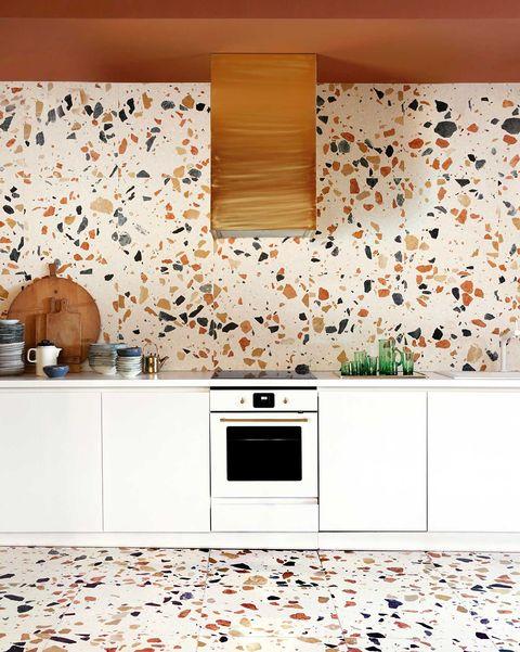 cocina con muebles blanco y paredes y suelo de terrazo