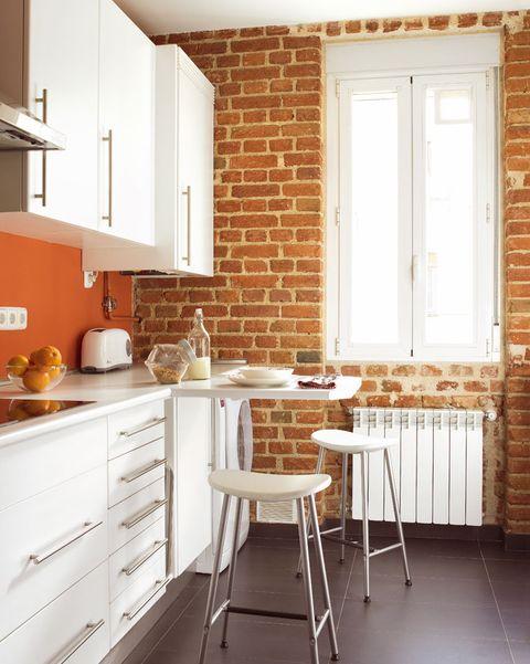 cocina pequeña con pared de ladrillo y muebles en blanco