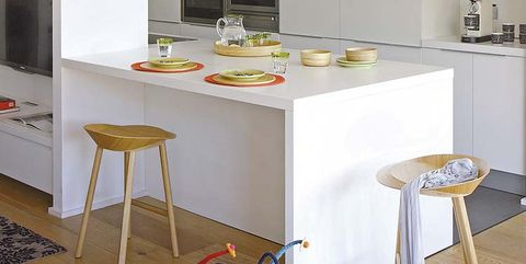 cocina blanca con isla y taburetes altos de madera