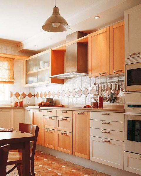 Una cocina con muebles blancos y de madera