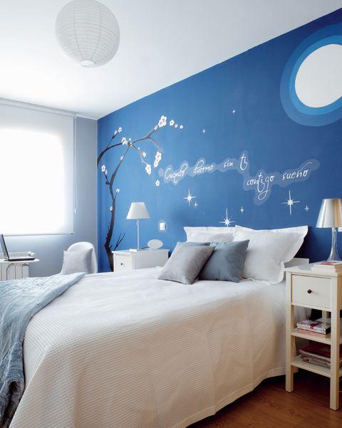 dormitorio con pared de cabecero azul