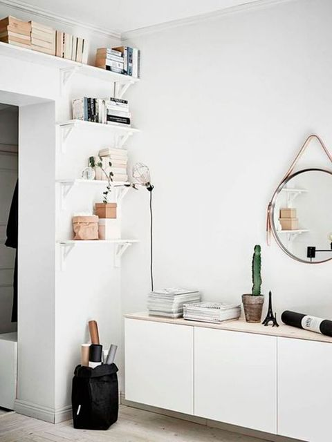 Un recibidor blanco con mueble bajo