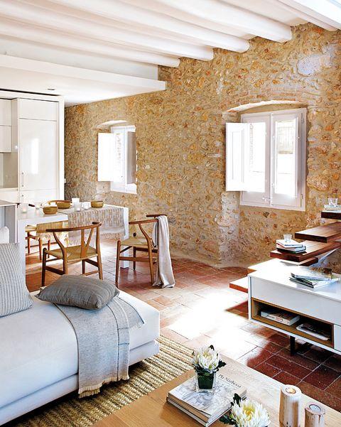 salón comedor con paredes de piedra y techo de vigas