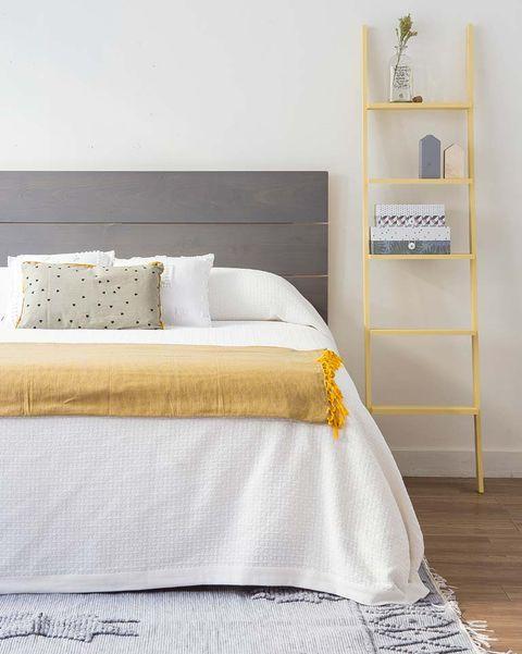 Dormitorio con escalera decorativa amarilla como mesilla