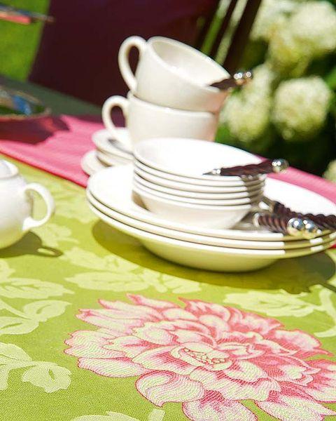 mesa puesta con mantel de flores y vajilla blanca