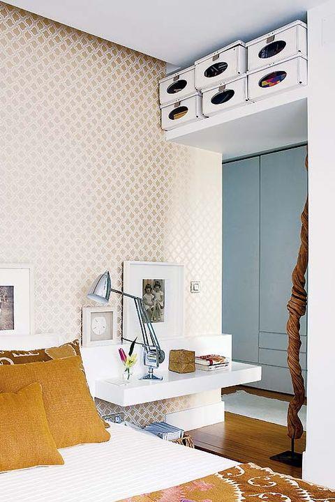 dormitorio con mesillas suspendidas y altillo sobre la puerta
