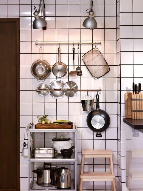 ollas y cacerolas en un soporte en la cocina