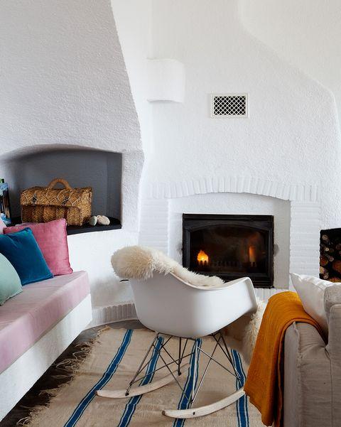 salón con chimenea de ladrillo pintado de blanco