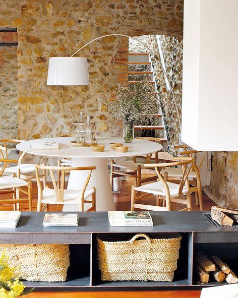 comedor con paredes de piedra y chimenea moderna