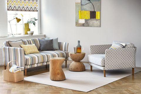salón moderno con mesas auxiliares de madera natural y sofá a rayas