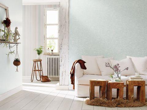 Salón con sofá blanco y mesas de madera rústica