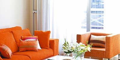 Room, Interior design, Living room, Furniture, Table, Orange, Couch, Home, Wall, Coffee table,