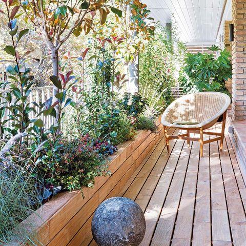 terraza con jardineras llenas de plantas y suelo de madera