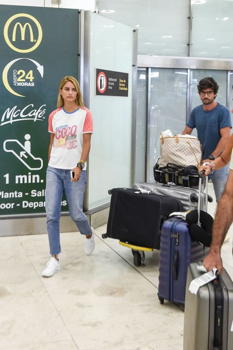 Denim, Jeans, Standing, Style, T-shirt, Luggage and bags, Travel, Baggage, Street fashion, Suitcase,