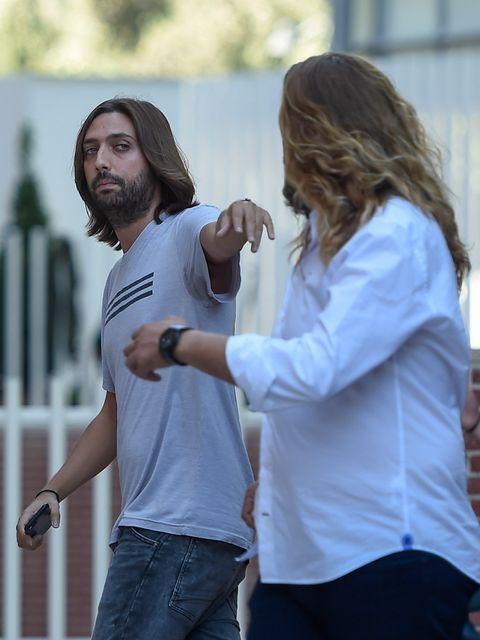 Hair, Hairstyle, Facial hair, Beard, Arm, Interaction, Gesture, Long hair, Hand, Jeans,