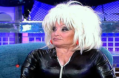 Nose, Hairstyle, Latex, Blond, Jacket, Leather, Wig, Costume, Latex clothing, Leather jacket,