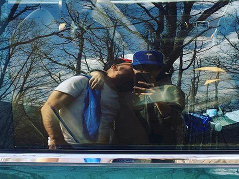 Cap, Interaction, Street light, Romance, Love, Electric blue, Display device, Baseball cap, Kiss,