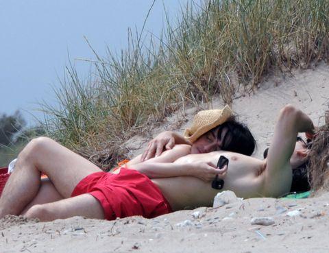 Human body, Sand, Human leg, Hat, Mammal, Summer, Sun tanning, Sitting, Vacation, Beauty,