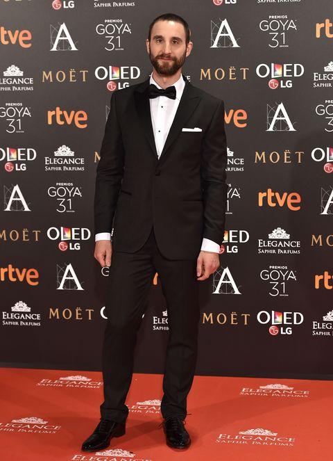Suit, Carpet, Red carpet, Tuxedo, Formal wear, Premiere, Font, Event, Flooring, Tie,