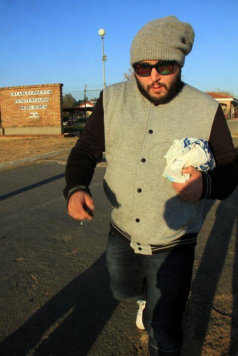 Cap, Textile, Hand, Facial hair, Jeans, Road surface, Denim, Asphalt, Sunglasses, Beanie,
