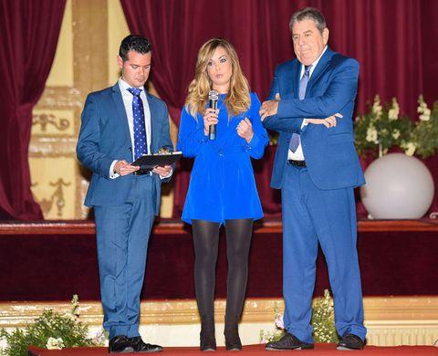 Textile, Suit trousers, Coat, Curtain, Dress shirt, Suit, Award, Blazer, Carpet, Cobalt blue,