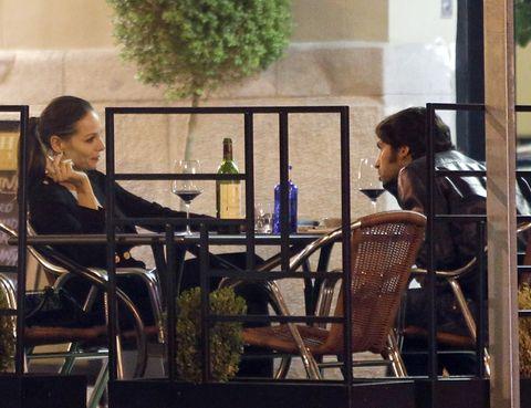 Furniture, Chair, Sitting, Table, Bottle, Drink, Wine bottle, Drinkware, Alcoholic beverage, Conversation,