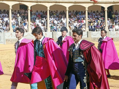 Matador, Tradition, Bullfighting, Event, Outerwear, Magenta, Performance, Sport venue, Temple,