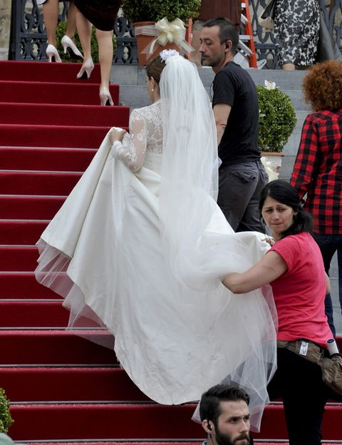 Trousers, Textile, Red, Dress, Stairs, Bridal veil, Veil, Bridal clothing, Wedding dress, Gown,