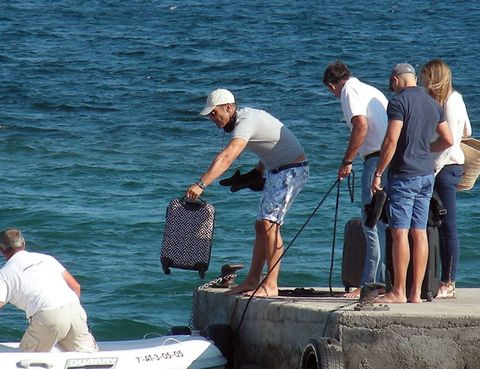 Human, Water, Mammal, Elbow, Tourism, Bermuda shorts, Back, Sun hat, board short, Boats and boating--Equipment and supplies,