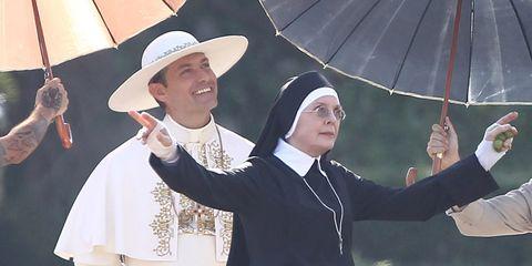 Hat, Costume accessory, Umbrella, Sun hat, Gesture, Tradition, Costume design, Costume hat, Drama, Acting,