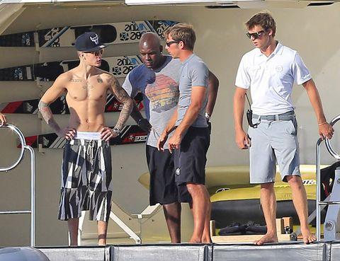 Eyewear, Standing, board short, Sunglasses, Shorts, Hat, Muscle, Active shorts, Bermuda shorts, Trunks,