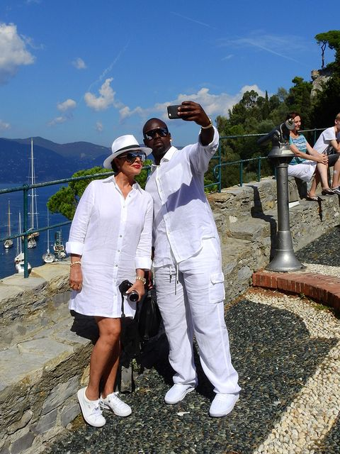 Footwear, Leg, Human, Tourism, Mountain range, Sunglasses, Sneakers, Walking shoe, Bermuda shorts, Sun hat,