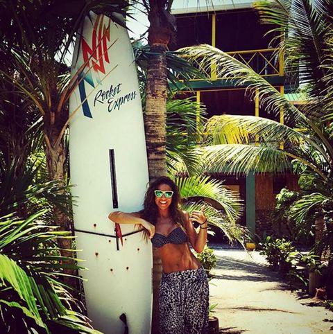 Arecales, Waist, Sunglasses, Street fashion, Trunk, Abdomen, Swimwear, Palm tree, Tropics, Surfboard,