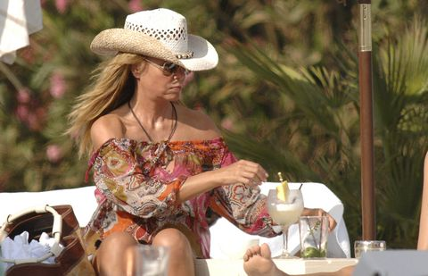 Hat, Dress, Fashion accessory, Drink, Sitting, Sun hat, Stemware, Drinkware, Wine glass, Fedora,