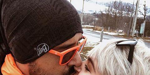 Ear, Forehead, Cap, Kiss, Love, Interaction, Romance, Fashion, Jacket, Facial hair,