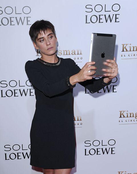 Dress, Little black dress, Joint, Gadget, Carpet, Technology, Electronic device, Photography, Flooring, Cocktail dress,
