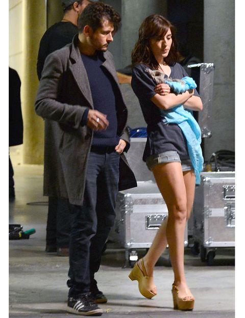 Clothing, Footwear, Leg, Microphone, Trousers, Human body, Coat, Shoe, Shirt, Human leg,