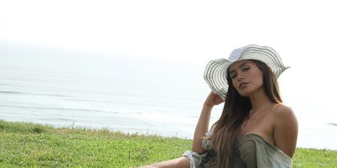 Clothing, Grass, Skin, Hat, Human leg, People in nature, Summer, Sitting, Dress, Sun hat,