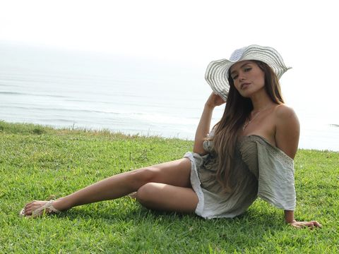 Clothing, Grass, Skin, Hat, Human leg, People in nature, Summer, Sitting, Dress, Sun hat,