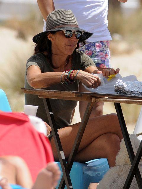 Eyewear, Vision care, Sitting, Hat, Hand, Summer, Table, Sunglasses, Headgear, Sun hat,