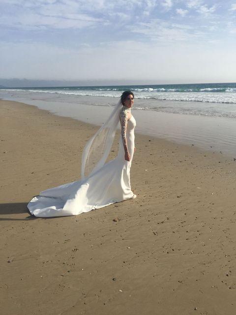 Clothing, Body of water, Natural environment, Coastal and oceanic landforms, Dress, Photograph, Sand, Wedding dress, Bridal clothing, Beach,