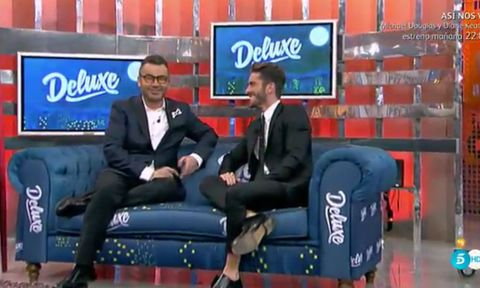 Clothing, Blue, Formal wear, Display device, Suit, Electric blue, Sitting, Logo, Television presenter, Couch,