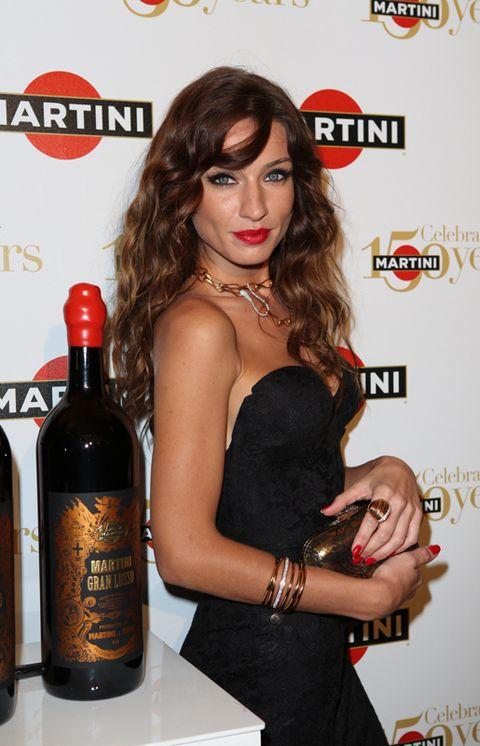 Bottle, Glass bottle, Hand, Drink, Alcohol, Alcoholic beverage, Dress, Logo, Distilled beverage, Brown hair,