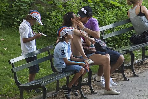 Leg, Bench, Hat, Human body, Sitting, Leisure, Outdoor furniture, Summer, Outdoor bench, People in nature,